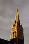 Spire of Christchurch Cathedral lit by morning sun under storm clouds, Christchurch, New Zealand