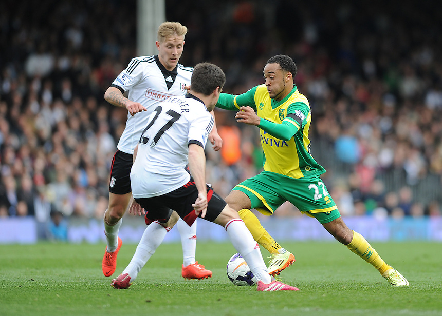 Norwich City's Nathan Redmond takes on Fulham's Sascha Riether and Lewis Holtby<br /> <br /> Photo by Ashley Western/CameraSport<br /> <br /> Football - Barclays Premiership - Fulham v Norwich City - Saturday 12th April 2014 - Craven Cottage - London<br /> <br /> &copy; CameraSport - 43 Linden Ave. Countesthorpe. Leicester. England. LE8 5PG - Tel: +44 (0) 116 277 4147 - admin@camerasport.com - www.camerasport.com