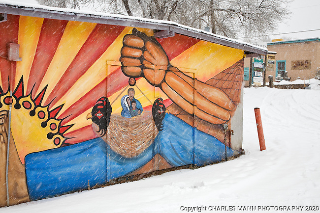 A colorful mural on a shed  on Canyon Road in Santa Fe seems to glow with color during a winter snowlfall.