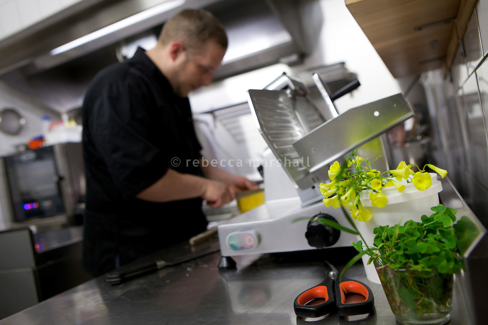 Mickaël Tourteaux cuts pineapple in the kitchen of Flaveur restaurant, Nice, France, 10 April 2012. Mickaël collected the wild yellow wood sorrel flowers (right of image) in the hills close to Nice uses them in certain dishes.