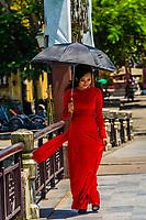 Vietnamese woman wearing traditonal Ao dai waling over a pedestrian footbridge, Hoi An, Vietnam.