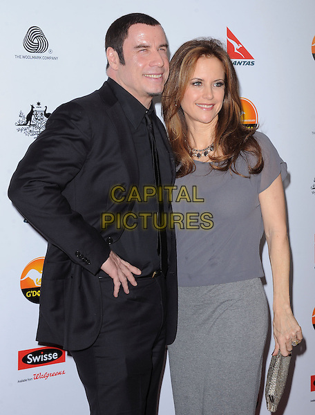John Travolta and Kelly Preston.at The G'Day USA Black Tie Gala held at The JW Marriot at LA Live in Los Angeles, California, January 12th 2013.                                                                 .half length grey gray top dress husband wife couple suit black shirt tie smiling goatee facial hair side clutch bag .CAP/DVS.©Debbie VanStory/Capital Pictures.