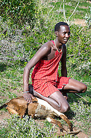 A Maasai warrior smothers a sheep, which will be roasted.