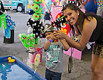 Mom Tami helps son Liam catch a fish on the Midway during the Reno Rodeo on Saturday, June 20, 2015.