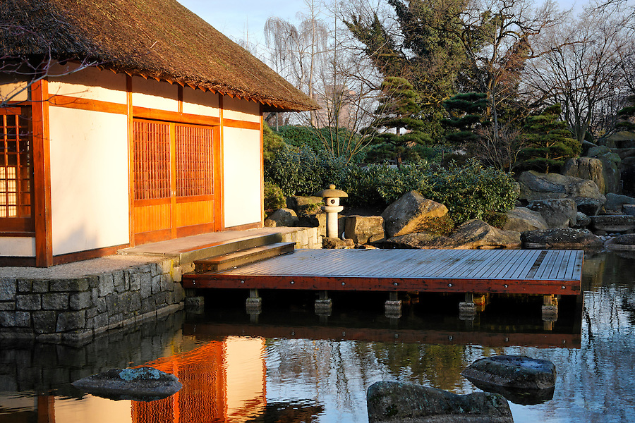 Tea house beside pond in Japanese Garden designed by landscape architect Joshikuni Araki in Hamburg's Planten un Blomen park, Germany