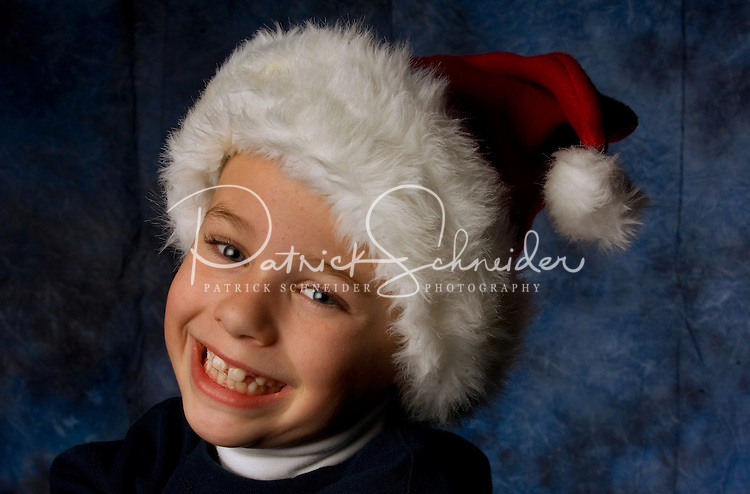 A young boy wearing a red and white Santa hat shows his joy that Christmas is coming.