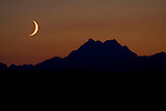 A waxing crescent moon sets over the Olympic Mountains  on Friday, July 24, 2009.In  the northern hemisphere, if the left side of the Moon is dark then the light part is growing, and the Moon is referred to as waxing (moving towards a full moon). If the right side of the Moon is dark then the light part is shrinking, and the Moon is referred to as waning (moving towards a new moon).  ©2014. Jim Bryant . All Rights Reserved