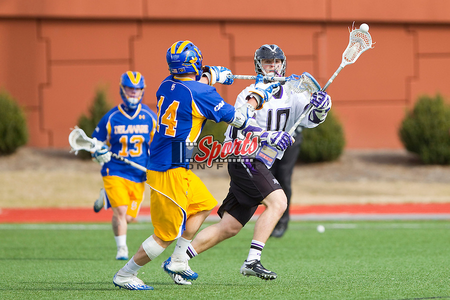 Brad James (10) of the High Point Panthers makes a pass while being defended by Sean Finegan (14) of the Delaware Blue Hens at Vert Track, Soccer & Lacrosse Stadium on February 2, 2013 in High Point, North Carolina.  The Blue Hens defeated the Panthers 12-10.   (Brian Westerholt/Sports On Film)