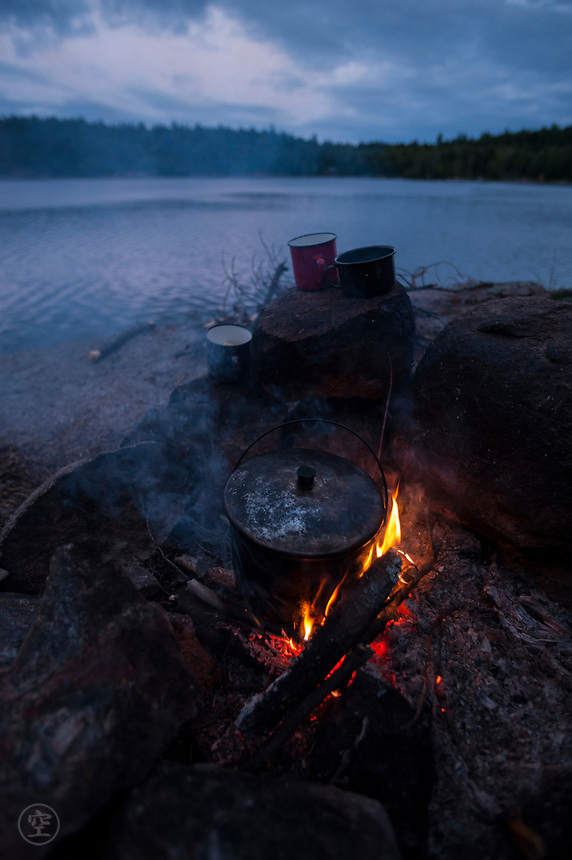 Camp fire and boiling camp kettle with three enamel cups on the shores of Johnny Lake, Killarney Provinical Park, Ontario, Canada