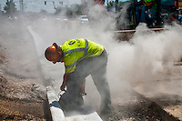 Concrete dust fills the air as a worker cuts expansion joints into freshly laid curbs on State Street.