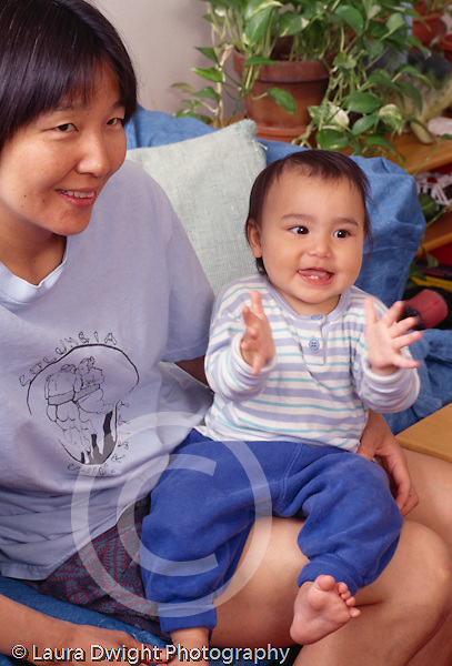12 month old baby boy sitting on mother's lap language development clapping hands horizontal