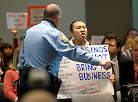 A capitol policeman removes protester Laihar Cheung, right, after she disrupted and shouted down Steve Wynn as he was addressing the Pennsylvania Gaming Control Board during a public hearing on the Foxwoods Casino issues Wednesday, Mar. 3, 2010 in Harrisburg, PA. Wynn was to address the board on his involvement with the Foxwood Casino development in Philadelphia. (Bradley C Bower/Bloomberg News)