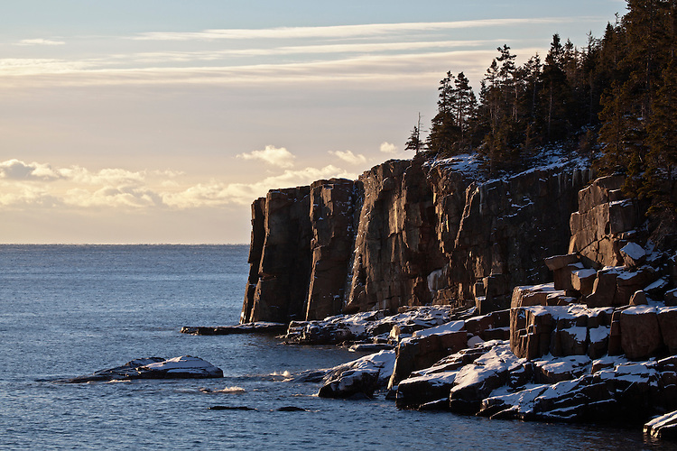 Snow and ice on the Otter Cliffs as viewed from Boulder Beach along Ocean Drive on Mount Desert Island in Acadia National Park, Maine, USA