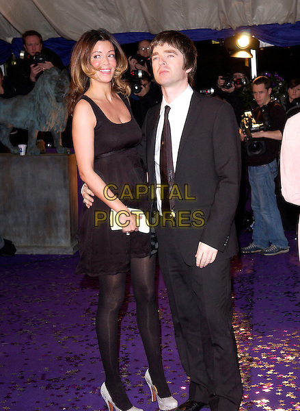 SARAH MacDONALD & NOEL GALLAGHER.British Comedy Awards 2004  - Arrivals.London Television Studios..December 22nd, 2004.full length, boyfriend, girlfriend, couple, arm around waist, black suit.www.capitalpictures.com.sales@capitalpictures.com.© Capital Pictures.