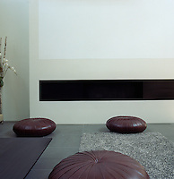 The floor of the living room functions as a seating area and is dotted with a collection of round leather pouffes