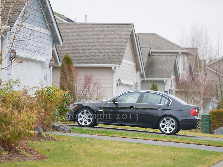 Black Car in Driveway of Blue Home