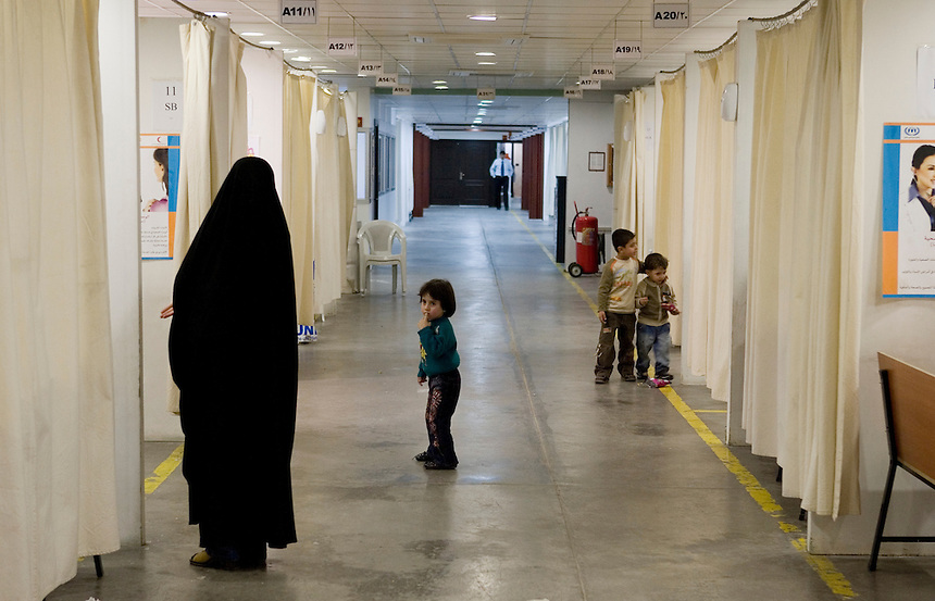 An Iraqi woman and children stand in a hallway prior to being interviewed for refugee status at a United Nations High Comissioner for Refugees (UNHCR) registration post on the outskirts of Damascus, Syria, November 19 2008. According to UNHCR, the post processed an average of 3000 new Iraqi refugees per month in 2008, down from a peak of 10 000 per month in late 2007. Photo: Ed Giles/REUTERS (Syria).