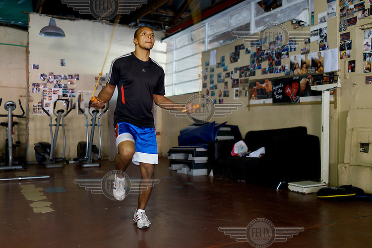 Siyakudumisa Vapi, a licensed boxer hoping to make it as a professional, skipping during training at the Hillbrow Boxing Club. He is training for a fight against the third-ranked fighter in the national featherweight division; if he wins it wil bring him closer to his objective of challenging for the national title, and being able to make a decent living from boxing. Vapi says boxing pulled him away from the streets and bad company, and gave him discipline.  Hillbrow, in downtown Johannesburg, is the city's most notorious neighbourhood. It is overcrowded, ridden with illegal squats and suffers from high levels of crime much of which is related the thriving illicit drug trade. The gym has become a place of hope and discipline for local youth, keeping them of the streets and even producing some national champions.