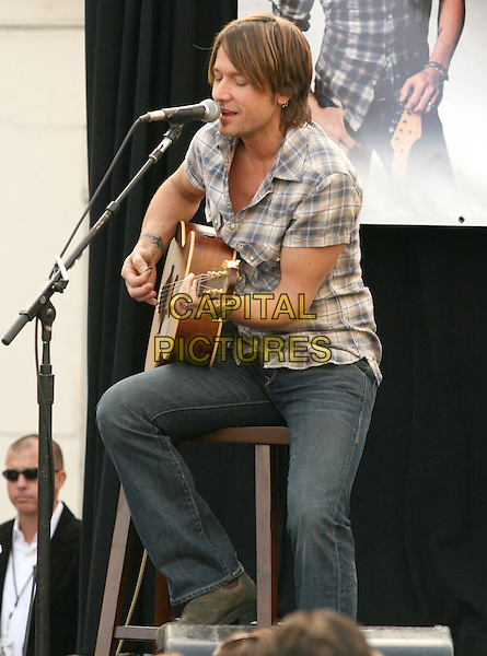 KEITH URBAN.is joined by Verizon Wireless and Samsung Mobile as he makes an in-store appearance for his fans at the Verizon Wireless store in Pasadena, California, USA, November 21st 2009                                                                   .full half foot length music concert gig live on stage grey gray brown plaid checked check shirt jeans sitting microphone singing playing tattoo bracelets guitar .CAP/RKE/DVS.©DVS/RockinExposures/Capital Pictures
