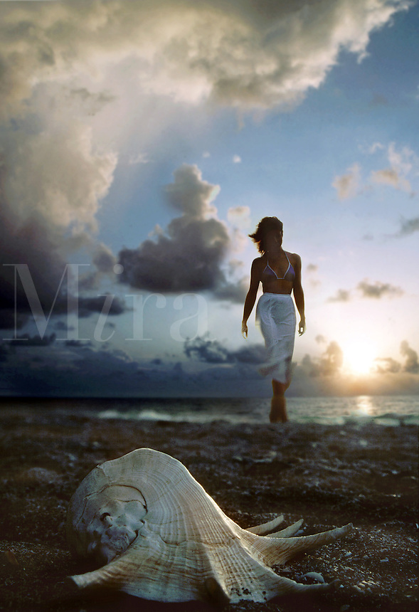 A woman walks on a beach under dramatic clouds and sunrise.