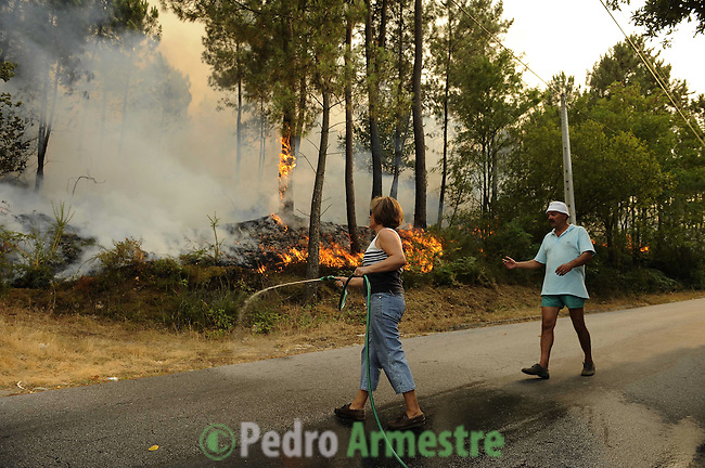 A man and his wife are seen around the area where a fire burns, in Salvador nord of Portugal, on august 09, 2010. (c) Pedro ARMESTRE