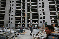 Migrant workers walk among unfinished buildings at the construction site of Changxiang Gardens development complex in Fengrun District, Tangshan City, Hebei province, China January 28, 2016. REUTERS/Damir Sagolj