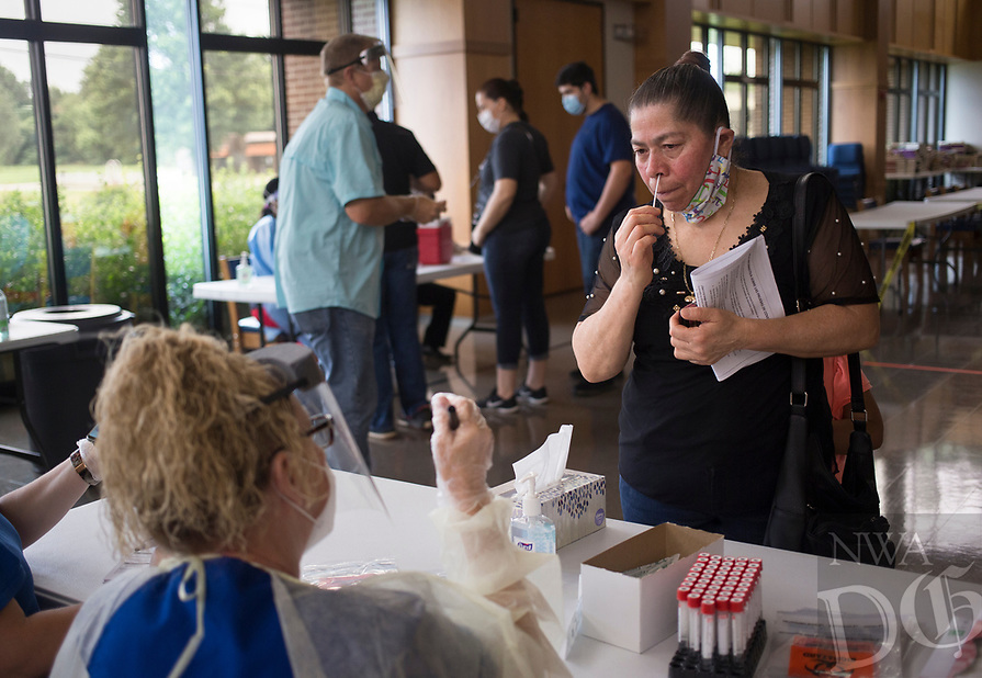 """Oltilia Zavala of Springdale (right) self-administers a covid-19 test, Sunday, June 28, 2020 at St. Raphael Catholic Church in Springdale. The Arkansas Department of Health partnered with the church to host a covid-19 screening for the parishioners of the church. Their goal was to administer 250 tests. """"They have a large Hispanic congregation greater than 70 percent so we're trying to offer it to their members,"""" said Cassie Cochran, Northwest Region Director. """"They're comfortable coming here, and it's convenient because they have eight masses on Sunday."""" The Arkansas Department of Health will hold another screening on Tuesday, June 30th at the Washington County Health Unit in Fayetteville that will be open to the general public from 4pm to 8pm. Check out nwaonline.com/200629Daily/ for today's photo gallery. <br /> (NWA Democrat-Gazette/Charlie Kaijo)"""