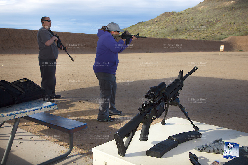 USA. Arizona state. Phoenix. Ben Avery Shooting Facility. The Ben Avery Shooting Facility, formerly the Black Canyon Shooting Range, is one of the largest publicly operated shooting facilities in the United States. Paula (R) holding an AR-15 and Greg (L) with an AR-15 and a suppressor, are a couple which trains their shooting skills with two semi-automatic rifles. In the forreground on a table, a Smith & Wesson M&P15-22 on a tripod with an optical gunsight and a magazin loaded with ammunition. The AR-15 is a lightweight, intermediate cartridge, magazine-fed, air-cooled Armalite Rifle. A suppressor, sound suppressor, sound moderator, or silencer is a device attached to or part of the barrel of a firearm which reduces the amount of noise and visible muzzle flash generated by firing. A firearm is a portable gun, being a barreled weapon that launches one or more projectiles often driven by the action of an explosive force. Most modern firearms have rifled barrels to impart spin to the projectile for improved flight stability. The word firearms usually is used in a sense restricted to small arms (weapons that can be carried by a single person). The right to keep and bear arms is a fundamental right protected in the United States by the Second Amendment of the Bill of Rights in the Constitution of the United States of America and in the state constitutions of Arizona and 43 other states. 28.01.16 © 2016 Didier Ruef