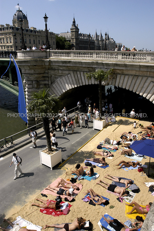 7/24/2004--Paris, France..The annual 'Paris Plage' (Paris beach) along the Seine River in the heart of Paris. Every year the city closes the road, brings in sand and palm trees to recreate the Riviera for those stuck in Paris during the Summer holidays.....Photograph by Stuart Isett.©2004 Stuart Isett. All rights reserved