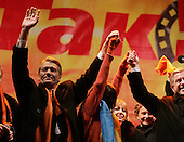 "Kiev, Ukraine.December 26, 2004..Opposition candidate Viktor Yushchenko takes center stage on Maidan Independence Square as thousands of Orange flag waving supporters rally to his side. Election polls show him in a strong lead just hours after the polling stations close. ..He is joined on stage by his wife Kathy, his son Andrey and his political partner Yulia Timoshenko. Holding his hand to the right is Ruslana, the famous Ukrainian singer who won the 2004 Eurovision song contest...The first round of voting was considered fraudulent when the ruling president Viktor Yahukovich won and the opposition candidate Viktor Yushchenko lost. ..Several hundred thousand Ukrainians took to the streets of Kiev and held daily rallies on Maidan Independence Square. The protests lasted nearly a month before the first vote was declared invalid and a new round of elections held on December 26, 2004. ..The demonstrations would come to be known as the ""Orange Revolution"" after the color of the opposition party."