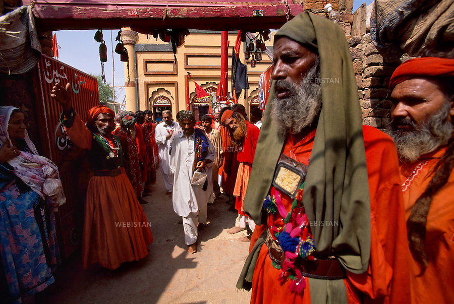 SEHWAN SHARIF, PAKISTAN - SEPTEMBER, 2006:  Group of dervishes known as Malang, waiting at the entrance of the shrine of Sufi Bodla Bahar to greet their sufi master (pir), Sheikh Akhtar Hussein Pirzada, titled as  Noor Ali Shah, during the annual celebration of Urs of Lal Shahbaz Qalandar, a 13th century Sufi Master worshiped alike by Hindus and Muslims. Born as Seyed Shah Hussain (Usman) Marandi, he later on titled as Lal (red) Shahbaz ( Falcon) Qalandar (as he belonged to Qalandria order of sufism).