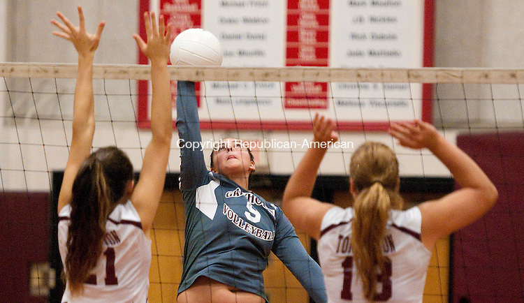 TORRINGTON, CT-100814JS17-  Naugatuck's  Ally Mezzo (9) spikes the ball past Torrington's  Miah Giarnese (21) and Caitlyn Cornish (18) during their match  Wednesday at Torrington High School. <br /> Jim Shannon Republican-American