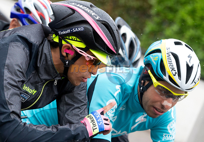 A well wrapped up race leader Alberto Contador (ESP) Tinkoff-Saxo chats with rival Fabio Aru (ITA) Astana at the start of a very wet Stage 13 of the 98th Giro d'Italia 2015 running 147km from Montecchio Maggiore to Jesolo. 22nd May 2015. <br /> Photo: ANSA/Claudio Peri/www.newsfile.ie