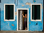 A woman closes her door curtain in the colorful village of Burano, Italy.