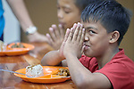 A boy smiles at the photographer as he prays before a meal in Knox United Methodist Church in Manila, Philippines. Once a week, the church opens up to poor residents of the neighborhood, offering food, showers, fellowship, a meal, worship, and an educational opportunity for the children.