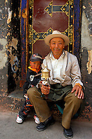 Tibetan Buddhist pigrim, with prayer wheel and rosary beads, resting with grandson in a typical Tibetan painted doorway in the the old section of the Tibetan quarter behind Meru Nyingba Monastery in the Barkhor area, Lhasa, Tibet.