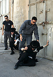 An ultra-Orthodox Jew is grabbed by an Israeli Border policeman during a protest in the coastal town of Jaffa, just south of Tel Aviv, on 29 August 2010 over the town's decision to remove ancient graves found during the construction of a hotel. Photo by Mahfouz Abu Turk