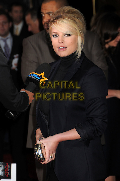 "JESSICA SIMPSON.""Extraordinary Measures"" Los Angeles Premiere held at Grauman's Chinese Theatre, Hollywood, California, USA..January 19th, 2010.half length black high collar beehive teased hair big sweeping fringe jacket top silver clutch bag microphone interview navy blue.CAP/ADM/BP.©Byron Purvis/AdMedia/Capital Pictures."