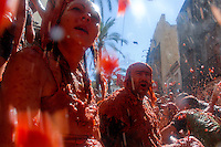 People splash tomato pulp during La Tomatina festival in Bunol, Spain, 31 August 2006. La Tomatina is a tomato fight held annually in the town of Bunol, close to Valencia. Approximately 40,000 people from all over the world arrive to fight in the battle in which about 50 tons of over-ripe tomatoes are thrown in the street. During the one hour battle everybody fights everybody by throwing squashed tomatoes. The origin of this event is unknown but the Tomatina fights have been recorded since 1945.