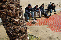 Moroccan immigrants sit on the beach and wait for the night to enter illegaly to the port of Tanger, Morocco, 22 October 2006. Every day tens of Moroccan young men try to cross ilegally the Strait of Gibraltar. ?Harraga? (immigrants in Arabic) come to Tanger from all over Morocco. They try their good luck and hidden between the wheels of a truck they attempt to board on a ferry and get to Spain, eventually further to Europe. Considering the thorough checks at the port only few of them make it. Therefore they spend months living on a beach, in huts along the walls of the port, begging for food and waiting for the right night so as their dream about Europe came true.