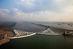 Nederland, Zuid-Holland, Nieuwe Waterweg, 19-09-2009; Functioneringssluiting Maeslantkering: de waterkering in de Nieuwe Waterweg wordt een maal per jaar, voordat het stormseizoen begint, getest. Tijdens  het sluiten van de kering ligt alle scheepvaartverkeer naar de Rotterdamse haven stil. Aan de horizon Rotterdam, rechts Callandkanaal en de havens van Europoort..De Maeslantkering sluit normaal gesproken alleen bij dreigende stromvloed en bij een waterstand van 3 meter of meer boven NAP. De kering, onderdeel van de Deltawerken, vormt samen met de Hartelkering de Europoortkering en beschermt Rotterdam en achterland bij extreme waterstanden. .Netherlands, Hoek van Holland - Rotterdam harbour. Aerial view of the new storm surge barrier (Maeslantkering) in the Nieuwe waterweg during the so-called functioning closure, taking place one a year before the storm season begins. The waterway, leading to the Port of Rotterdam (at the horizon), is closed during the test..luchtfoto (toeslag), aerial photo (additional fee required).foto/photo Siebe Swart