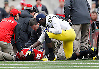 Michigan Wolverines quarterback Devin Gardner (98) grabs the head of quarterback J.T. Barrett (16) after he went down with an ankle injury during the 4th quarter of the NCAA football game at Ohio Stadium on Nov. 29, 2014. (Adam Cairns / The Columbus Dispatch)