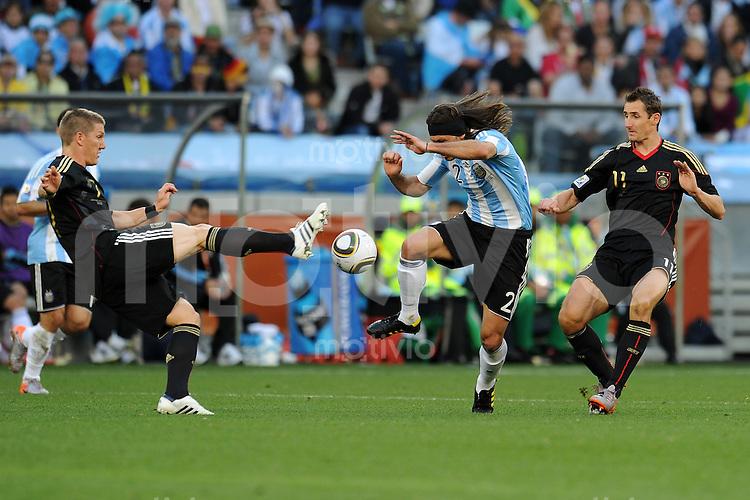 FUSSBALL WM 2010    VIERTELFINALE  03.07.2010 ARGENTINIEN - DEUTSCHLAND Bastian SCHWEINSTEIGER (li) und Miroslav KLOSE (re, beide Deutschland) gegen Martin DEMICHELIS (Mitte, Argentinien)