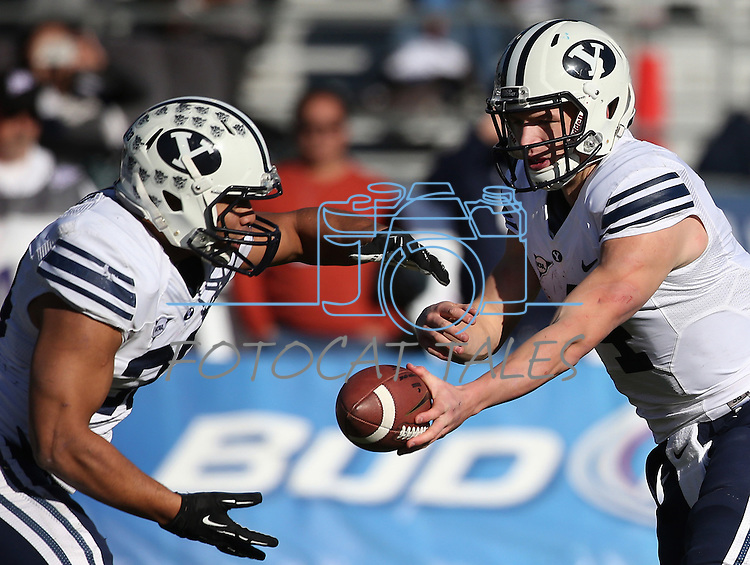 BYU's Robertson Daniel (4) hands off to Paul Lasike (33) during the first half of an NCAA college football game against Nevada, in Reno, Nev., on Saturday, Nov. 30, 2013. (AP Photo/Cathleen Allison)