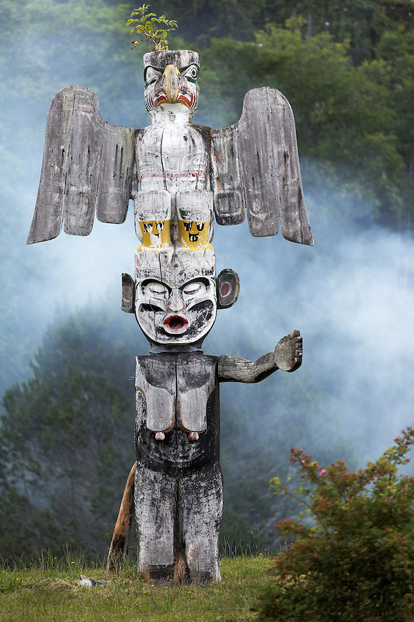 Totem pole in cemetery, smoke in background, Alert Bay, Vancouver Island, Canada