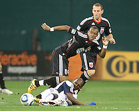 Rodney Wallace #22 of D.C. United is tackled by Emmanuel Osei #5 of the New England Revolution during an MLS match on April 3 2010, at RFK Stadium in Washington D.C. New England won 2-0.