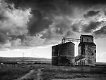 Idaho, Eastern, Tetonia. Grain elevators under a stormy sky.
