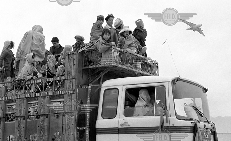 A Soviet IL-76 cargo jet comes in for landing in Kabul over the heads of Afghans using a lorry for transport on January 17, 1989. Under siege for several years, the regime in Kabu depends heavily on Soviet military support.