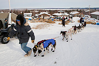 Volunteer in Shageluk helps Bob Bundtzen maneuver his dogs out of the Shageluk checkpoint during Iditarod 2009