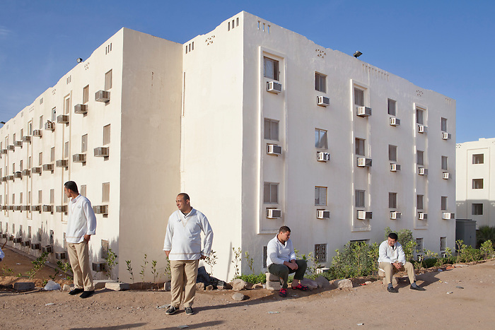 Sharm el Sheikh, Sinai, March 2015. Employees of the hotels waiting for the bus which will take them to work. The owners lodge their employees in one building, often in one of the tourist's bungalow. The seasonal workers come from Cairo, Mina or Alexandria. They live in the Sinai region during the time of their employment. Instead of employing the local Bedouin people, the owners tend to ignore them, hence increasing the unemployment rate which has razed since the revolution.